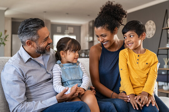 Happy ethnic family with two kids on couch