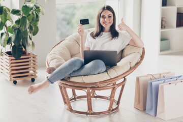 Full body photo of positive girl show order purchase through laptop show thumb-up sign sit wicker chair in house indoors
