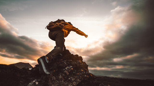 Hiker standing on the cliff mountain pointing the sky with fingers at sunset. Man on rocky cliff watching down to landscape. Focus on shoe.