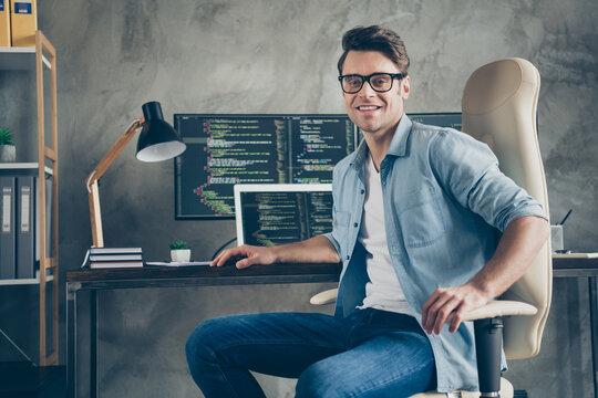 Portrait of positive guy it specialist sit chair desk enjoy working pc home ready debugging java script cyber space error wear denim jeans shirt in workplace