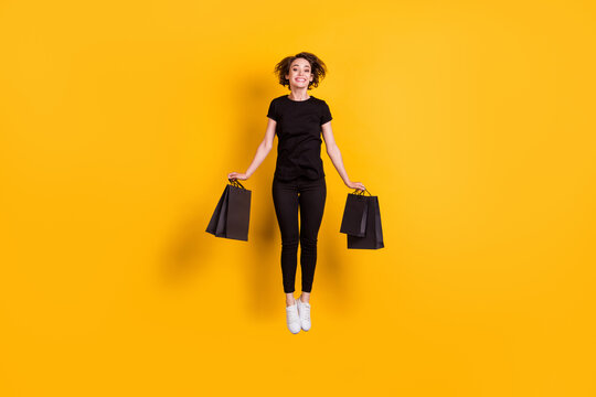 Full length body size view of attractive cheerful funky girl jumping carrying packages bargain store isolated bright yellow color background