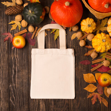 Tote bag with pumpkins, apples, nuts and autumn leaves on rustic wooden background.