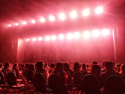 Blurred crowd at social distancing concert venue in Thailand during the coronavirus (covid-19) : Silhouette happy people sitting in front of stage with bright laser light beam.The New Normal