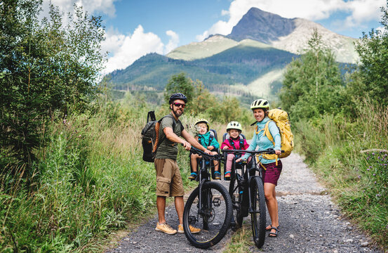 Family with small children cycling outdoors in summer nature.