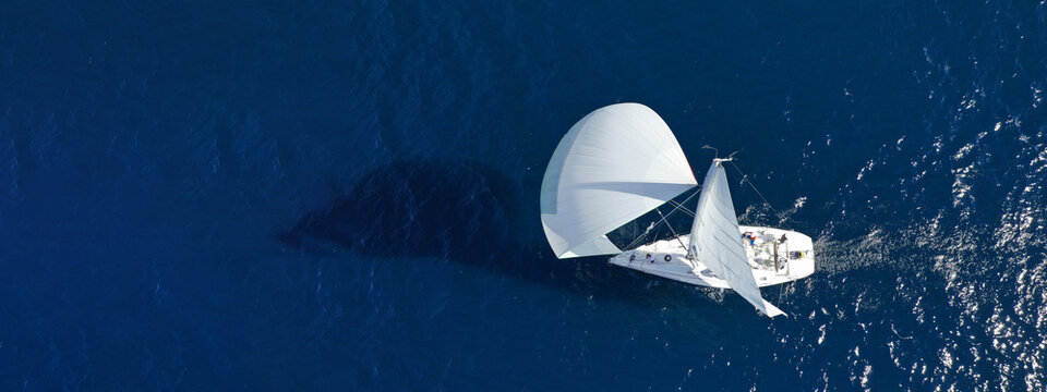 Aerial drone ultra wide panoramic photo of beautiful sailboat with white sails cruising deep blue sea near Mediterranean destination port