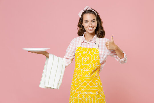 Cheerful smiling young woman housewife 20s in yellow apron hold empty plate dishcloth towel showing thumb up doing housework isolated on pastel pink background studio portrait. Housekeeping concept.