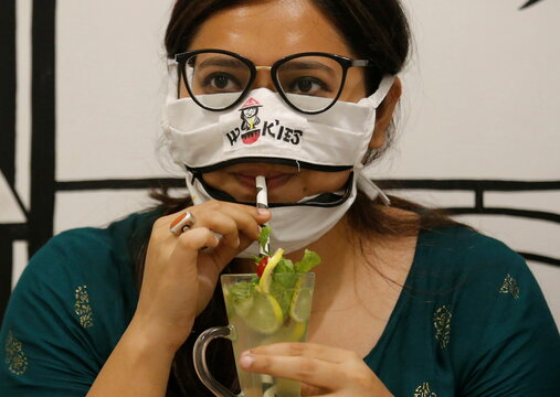 Woman drinks juice using zip-up mask provided by Wok'ies restaurant in Kolkata