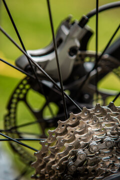 He looked down at the gears and the chain and gearbox of the mountain bike. The gear chains are very washable and greasy, and the hydraulic disc brake mechanism can be seen behind.