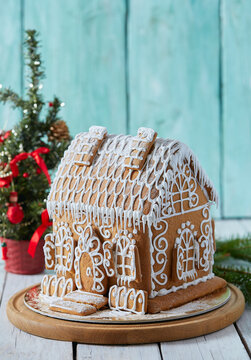 gingerbread house over turquoise wooden surface