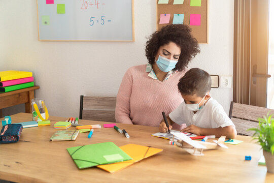 Teacher and child wearing protective face masks in classroom during coronavirus outbreak - Back to school during Covid-19 time concept - Soft focus on woman face