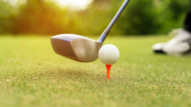 Close up Golf club hitting golf ball along fairway towards green with copy space, green nature background. Lifestyle and Healthy Concept. .