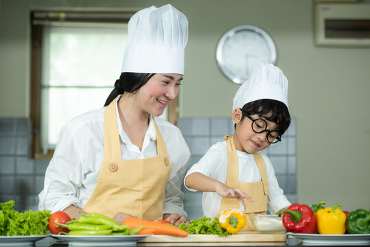 Cooking Family. Chef kid boy and mother making and leaning fresh vegetables salad for healthy eat and education.  Asian son helping make food,