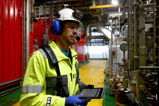 Sollid, a process technician at Equinor's Johan Sverdrup field holds a tablet he is using to inspect equipment on the platform in the North Sea