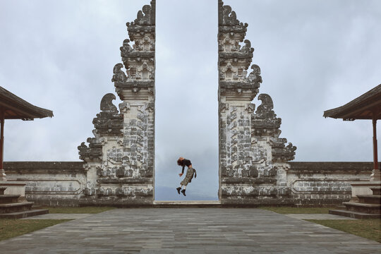 Beautiful Girl's Full-Length Portrait Near Gates Of Heaven In Pura Lempuyang Temple In Bali, Indonesia. Happy Young Woman Doing Back Band Jump Near Ancient Architecture In Asia.
