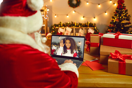 Santa Claus video calling a happy African American girl to wish her Merry Christmas