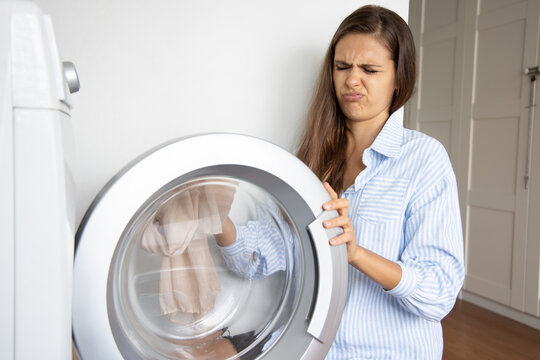 unhappy woman doing laundry howsework, washing dirty stinking cloth with laundry machine
