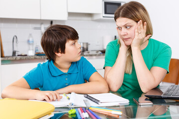Portrait of emotional woman and boy doing homework with laptop at kitchen