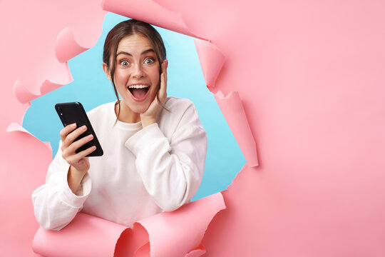 Caucasian young woman expressing surprise while holding cellphone