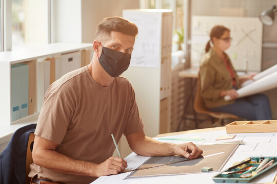Portrait of mature bearded architect wearing mask while sitting at drawing desk in sunlight, copy space