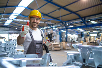 Fototapeta Portrait of factory worker in protective equipment holding thumbs up in production hall. obraz