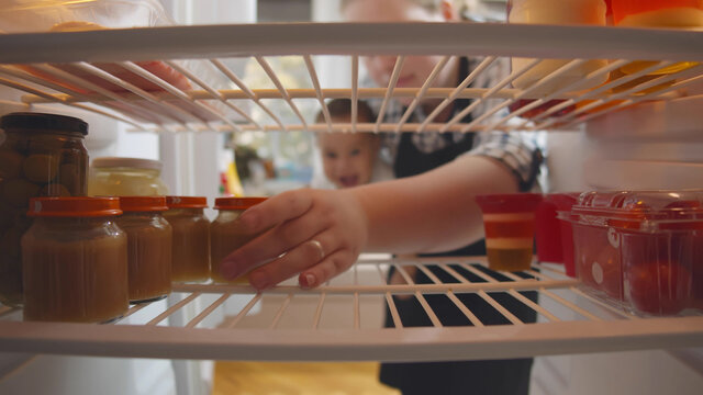 Mother with baby in hands opening fridge and taking glass jar of baby food
