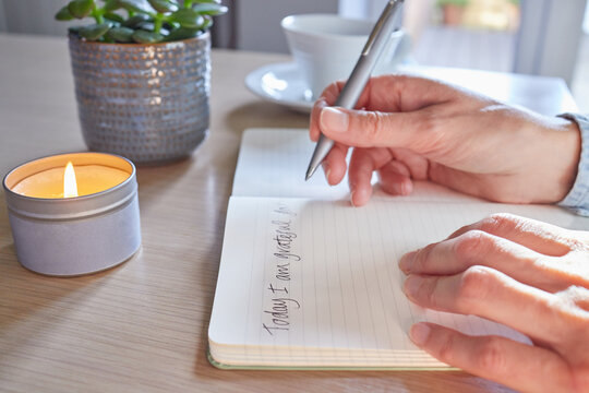 Close Up Of Woman At Home Writing In Gratitude Journal