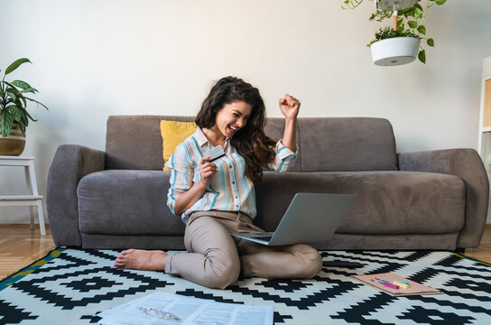 Excited woman holding credit card and using laptop computer stock photo
