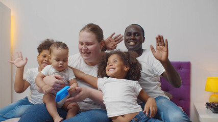 Family portrait of beautiful mixed race kids with multi-ethnic parents waving hands at camera