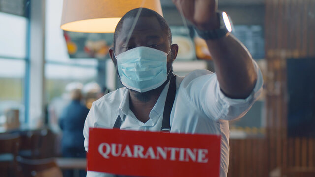 Afro-american waiter wearing safety mask hanging quarantine sign in glass door of cafe