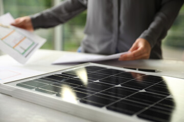 Solar panel and blurred person with papers on background, closeup