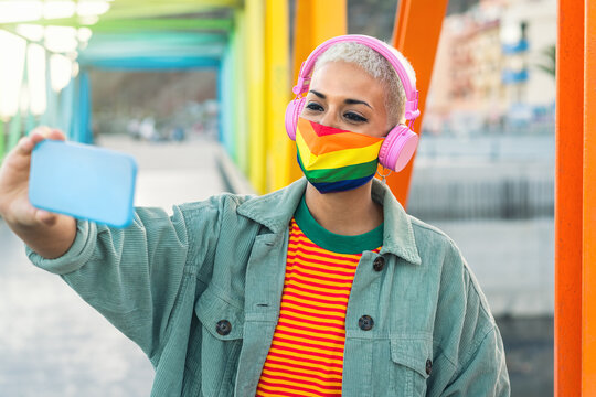Young woman wearing gay pride mask listening to music with wireless headphones and taking selfie with mobile smartphone outdoor - Gender equality and technology concept