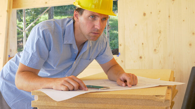 CLOSE UP: Worried carpenter looks around the room while analyzing the blueprints
