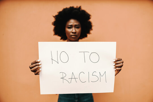 Young african woman holding paper with NO TO RACISM title.