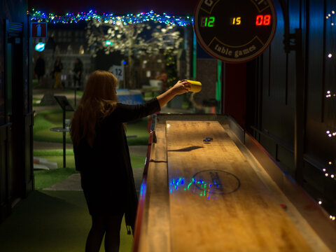 Stockholm, Sweden - October 6 2018 : Woman pouring sand on shuffleboard table on a bar
