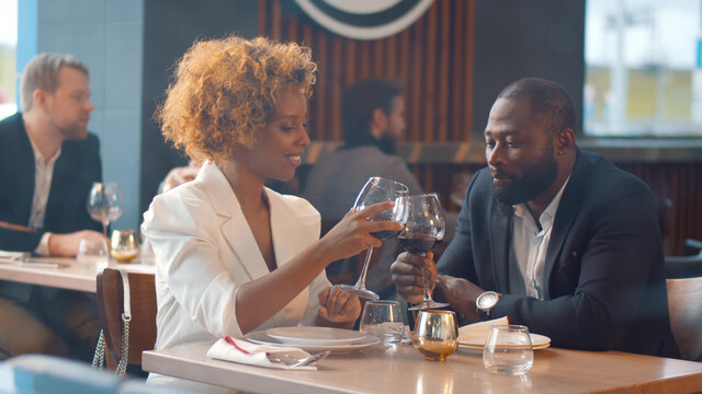 Young loving african couple sitting in modern restaurant smiling and clinking glasses with wine