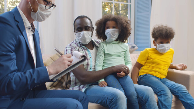 Insurance agent in mask consulting smiling young african man with kids at home.