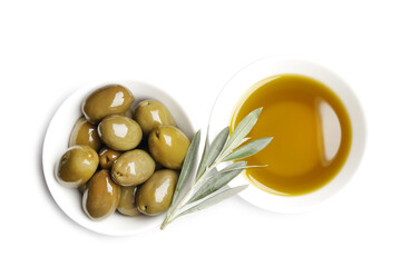 Bowl of fresh olive oil and green olives with leaves isolated on white background. View from above