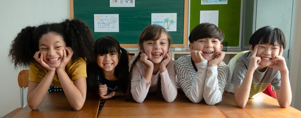 Portrait of happy elementary international students sitting on desk touches cheeks with both hands...