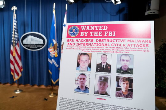 A poster showing six wanted Russian military intelligent officers is displayed before a news conference at the Department of Justice, in Washington
