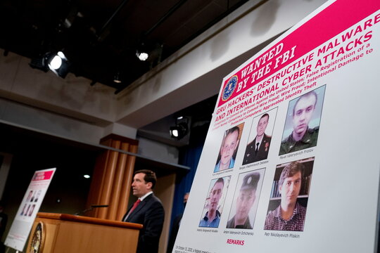 Posters showing six wanted Russian military intelligence officers is displayed as Assistant Attorney General for the National Security Division John Demers speaks at a news conference at the Department of Justice, in Washington