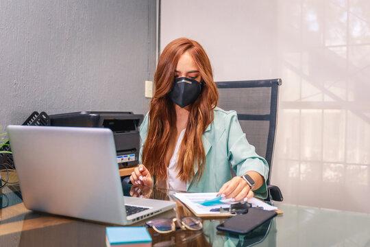 mujer joven empresaria emprendimiento trabajando durante pandemia con mascarilla facial protección