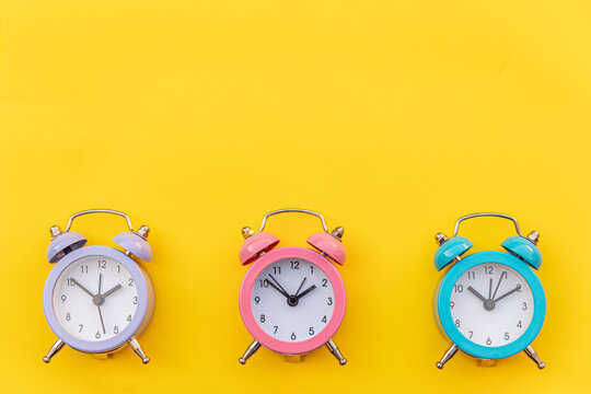 Simply minimal design three ringing twin bell classic alarm clock Isolated on yellow background. Rest hours time of life good morning night wake up awake concept. Flat lay top view copy space.