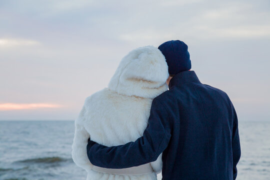 Man in black warm overcoat hugging woman in white fur coat. Young couple standing and staring at small waves of sea and overcast sky. Peaceful atmosphere in cold winter day. Back view.