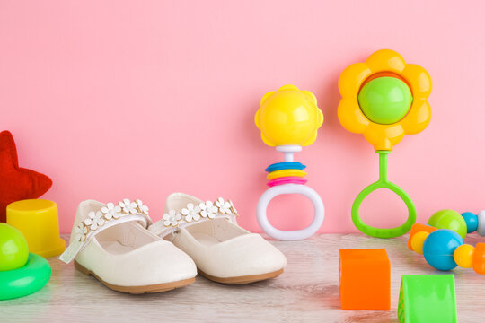 Baby white shoes, colorful different rattles and playing shapes on wooden floor at light pink wall in nursery room. First steps in kindergarten. Interesting toys for little kids. Closeup. Front view.