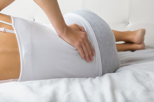 Young adult woman lying down on bed and touching her painful back with hand. Body health problem. Closeup.