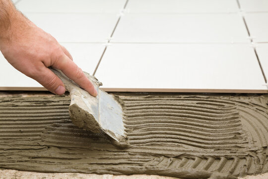 Worker hand using spatula and putting glue on floor. Gluing ceramic tiles. Closeup. Side view.