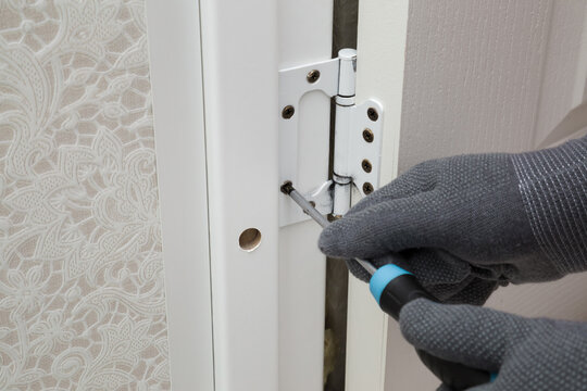 Man hands in protective gloves using manual screwdriver and screwing hinges on frame of wooden door to wall in bathroom. Closeup. Repair work of home. Renovation process.