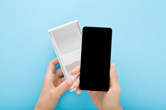 Young woman hand taking out new smartphone from white box on light blue table background. Pastel color. Closeup. Empty place for text on black screen. Point of view shot. Top down view.