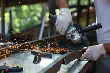 a worker cuts metal with a grinder close up