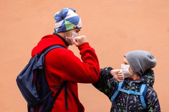 students in protective masks greet each other with their elbows